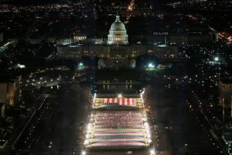 "The ""Field of Flags"" is illuminated on the National Mall as the U.S Capitol Building is prepared for the inauguration ceremonies for President-elect Joe Biden on January 18, 2021 in Washington, DC. Approximately 191,500 U.S. flags will cover part of the National Mall and will represent the American people who are unable to travel to Washington, DC for the inauguration. Joe Raedle/Getty Images/AFP"