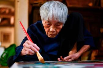 This photograph taken on October 8, 2020 shows 89-year-old Vietnamese artist Mong Bich painting at her house in Bac Ninh province, east of Hanoi. AFP / Manan VATSYAYANA