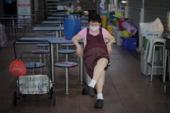A hawker wearing a face mask rests in a food centre in Singapore, 28 May 2020. - EPA