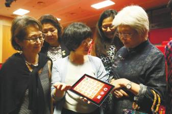 Lee (centre) showing an e-learning application to Chong (right). - Sunpix by Masry Che Aini