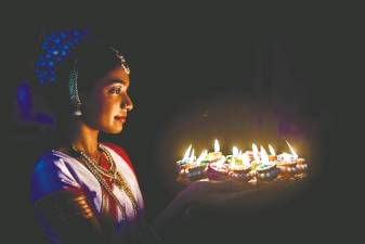 Lighting up colourful clay lamps in preparation of Deepavali. – AFP