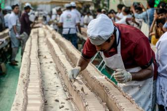 A baker prepares an approximately 6.5-km long cake in an attempt aim to break the Guinness World Record for the longest cake, in Thrissur in the south Indian state of Kerala on January 15, 2020. © Arun SANKAR / AFP