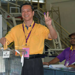 Barisan Nasional's candidate for the Tanjung Piai by-elections, Datuk Seri Dr Wee Jeck Seng, gestures the peace sign to cameras, as he casts his vote, at SJK (C) Yu Ming 1 & 2, in Pekan Nanas, on Nov 16, 2019. — Bernama