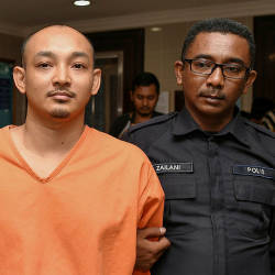 Mohd Nasli Mohd Nasir (L) is led out of the Kuala Terengganu sessions court, on Aug 22, 2019. — Bernama