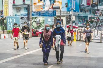 People walking outside a shopping mall in Kuala Lumpur. It is hoped that the budget's expansionary approach will boost overall consumer and business spending which in turn will translate into a second round effect that will benefit the rest of the economy. – AFPPIX