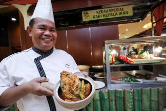 Chef Yusoff with fish head curry. - HAFIZ SOHAIMI/THESUN