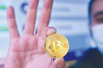 A man holding a physical imitation of a Bitcoin. Cryptocurrencies have been among the big winners this year, with Bitcoin leading the surge with a year-to-date gain of 232.7% as of 10pm yesterday. – AFPPIX