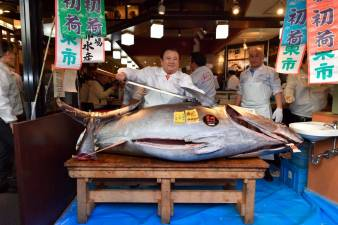 Kiyoshi Kimura (L), president of Kiyomura Corp., the Tokyo-based operator of sushi restaurant chain Sushizanmai, looks on as employees slice up a bluefin tuna the company bought for 193.2 million yen (1.8 million USD) at auction at his main restaurant in Tokyo on January 5, 2020. / AFP / Kazuhiro NOGI