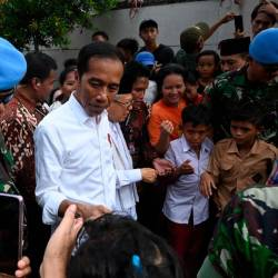 Indonesian President Joko Widodo (C) and his running mate Ma'ruf Amin (center R) speak with residents in a neighbourhood in Jakarta on May 21, 2019. - AFP