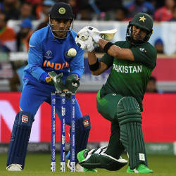 Pakistan's Rahat Ali (right) plays a shot watched by India's Mahendra Singh Dhoni (left) during the 2019 Cricket World Cup group stage match between India and Pakistan at Old Trafford in Manchester, England, on June 16, 2019.