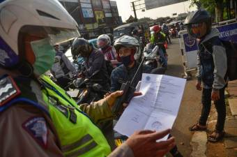 An Indonesian police officer inspects a document from a motorist heading toward the capital city of Jakarta, in Bekasi, West Java, on May 29, 2020, amid travel restrictions during the Covid-19 coronavirus pandemic. - AFP