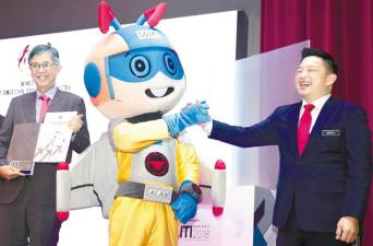 Chua (left) and Leiking with MPC's mascot at the launch of the Miti Report 2018 and Productivity Report 2018/2019. – Zulkifli Ersal/THESUN