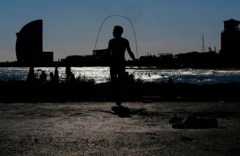FILE PHOTO: A man skips rope as he exercises at Barceloneta beach, after Spain's Catalonia region said it would allow gyms to reopen from Monday amidst the coronavirus outbreak, in Barcelona, Spain November 22, 2020. REUTERS/Nacho Doce/File Photo