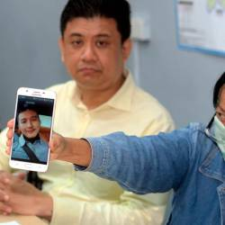 Stulang state assemblyman Andrew Chen Kah Eng (L) and Miss Lee, shows a picture of a foreigner involved in a 'love scam' syndicate during a press conference at the Stulang state assemblyman service centre today. - Bernama