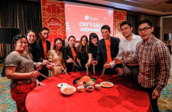 Tossing the yee sang at the Shopee Chinese New Year celebration. – Ashraf Shamsul/theSun