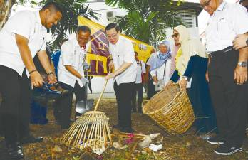 Lim (centre), who is also Bagan MP, participates in a gotong-royong campaign to clean up Taman Bagan Baru after launching the Kampungku Sihat programme on Sunday. – BERNAMAPIX