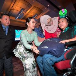 From left: Mak, Lee and RTM personnel presenting a hamper to a special needs child at the iftar event. SUNPIX by MASRY CHE ANI