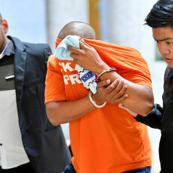 The accused (C) is led out of the magistrate's court in Putrajaya, on May 20, 2019. — Bernama