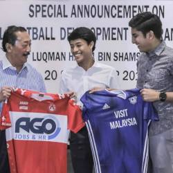 Berjaya Corporation Founder and Belgian football club KV Kortrijk owner Tan Sri Vincent Tan (left) together with striker Luqman Hakim Shamsudin (centre) after the signing. With them is Youth and Sports Minister Syed Saddiq Syed Abdul Rahman (right). — Sunpix by Adib Rawi