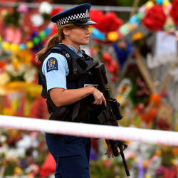 A policewoman patrols past a memorial wall outside the Linwood Mosque in Christchurch — AFP