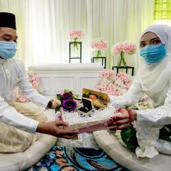 Abdul Khalib Abdullah (L) and his bride Nurul Fatihah Mat Husin, pose for a photo after their solemnisation ceremony, on April 4, 2020. — Bernama