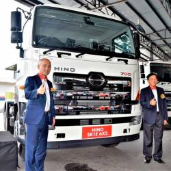 HMSM managing director Atsushi Uchiyama (left) and HMSM executive director Datuk Johnny Chan officially introducing the new variation of Hino 700 Series AMT models. Behind them is a SR1E 6x2 variant.