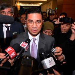 Economic Affairs Minister Datuk Seri Mohamed Azmin Ali responds to reporters questions after attending a PKR political bureau meeting at Parliament today. - Bernama