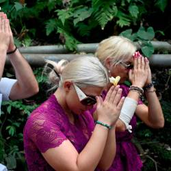 Czech nationals Sabina Dolezalova (centre R) and her boyfriend Zdenek Slouka (L) pray ahead of a purification ritual at the Beji Temple, located inside a monkey sanctuary in Ubud on Indonesia's resort island of Bali on Aug 15, after a disrespectful online video they posted went viral. — AFP