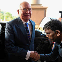 Datuk Seri Najib Abdul Razak shakes hands with a supporter as he arrives at the Kuala Lumpur High Court for his trial, on Aug 19, 2019. — AFP