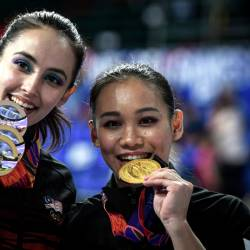 Artistic gymnastics athletes, Farah Ann Abdul Hadi (L) and Tracie Ang showing medals won respectively on the fourth day of the 30th SEA Games yesterday. — Bernama