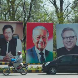 Pakistani peoples ride past the portraits of Prime Minister Imran Khan (L), President Airf Alvi (R) along with Malaysia's Prime Minister Mahathir Mohamad (C) on the Constitution avenue in Islamabad on March 21, 2019. — AFP