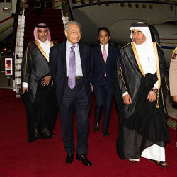 Prime Minister Tun Dr Mahathir Mohamad is greeted by Qatari Minister of Trade and Industry Ali bin Ahmed Al Kuwari (second from right) in Hamad International Airport at Qatar yesterday — Bernama