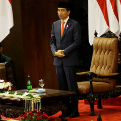 Indonesian President Joko Widodo stands after he was sworn in as president at the parliament building in Jakarta on Oct 20, 2019. — AFP
