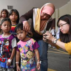 Filepix taken on Oct 12 shows Sri Rahayu Sugiono showing burns on her daughter Nur Haffiqah Khalid (C), 4, after her family were released from Putrajaya Hospital after being hit by a helium balloon blast. — Bernama