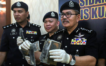 Kuala Lumpur police chief Commissioner Datuk Seri Mazlan Lazim reveals the items seized during a press conference on a 'black money' fraud syndicate at the Kuala Lumpur police headquarters today. — Bernama