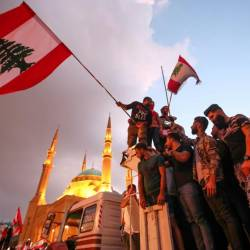 Lebanese demonstrators wave national flags as they take part in a rally in the capital Beirut's downtown district on Oct 20, 2019. — AFP