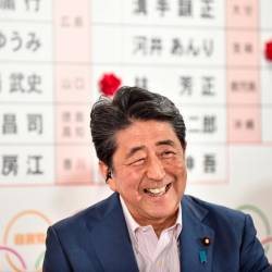 Japanese Prime Minister and ruling Liberal Democratic Party (LDP) president Shinzo Abe smiles as he responds to questions during a television interview following the Parliament's upper house election at the party's headquarters in Tokyo on July 21, 2019. — AFP