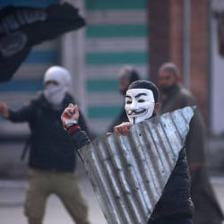 A demonstrator wearing a Guy Fawkes mask throws a stone towards the Indian police during a protest after Friday prayers, in Srinagar Dec 14, 2018. — Reuters