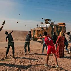Syrians throw stones towards Turkish military vehicles during a Turkish-Russian army patrol near the town of Darbasiyah in Syria's northeastern Hasakeh province along the Syria-Turkey border on Nov 11. — AFP