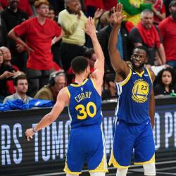 Stephen Curry #30 of the Golden State Warriors high fives Draymond Green #23 during the second half against the Portland Trail Blazers in game four of the NBA Western Conference Finals at Moda Center on May 20, 2019 in Portland, Oregon. - AFP