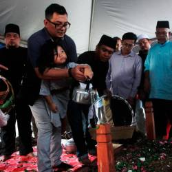 Eva Arianna, 4, poured roses and water onto the body of her father, Datuk Dr Md Farid Md Rafik, after the body was buried at the Sheikh Haji Ahmad Waqf Muslim Cemetery in Kampung Chokoh, Serkat, at 5.30pm on Sept 22, 2019. - Bernama