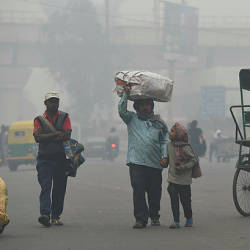 A family carries belongings while looking for a rickshaw amid heavy smog in New Delhi. — AFP