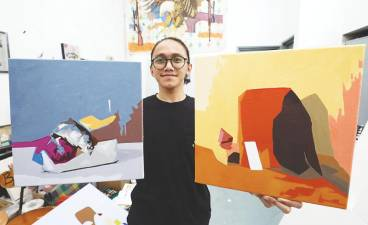 Aleff with two of his completed paintings. – MASRY CHE ANI/THESUN