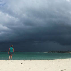 A woman walks on the beach as a storm approaches in Nassau, Bahamas, on September 12, 2019.