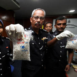Port Dickson District Police chief Supt Aidi Sham Mohamed and other police personnel show off some of the seized heroine and syabu, during a press conference at Port Dickson District Police Headquarters on Feb 15, 2019. — Bernama