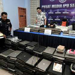Police display the devices seized during the raids. — Bernama