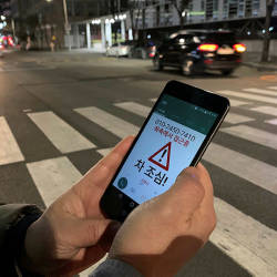 Kim Jong-hoon, a senior researcher at Korea Institute of Civil Engineering and Building Technology (KICT) demonstrates an application 'Watch Out' that gives an alert to a user distracted by using smart phone while crossing a zebra crossing, in Ilsan, South Korea, March 12, 2019. — Reuters