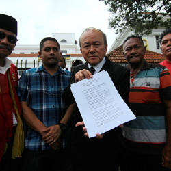 Lawyer Kamaruddin Ahmad (center) together with plaintiffs showing a list of defendants' names in a summons at a press conference at Johor Baru High Court today.