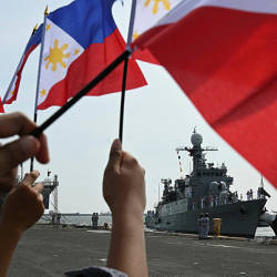 Relatives of Philippine Navy sailors wave their national flags as the navy's newly-acquired vessel, the Pohang-class corvette BRP Conrado Yap (PS39), docks at the international port in Manila on Aug 20, 2019. — AFP