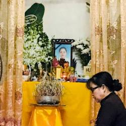 A woman prays at an altar with an image of Pham Thi Tra My, a victim of 39 deaths in a truck container in UK, at her home in Ha Tinh province, Vietnam October 27, 2019. - Reuters